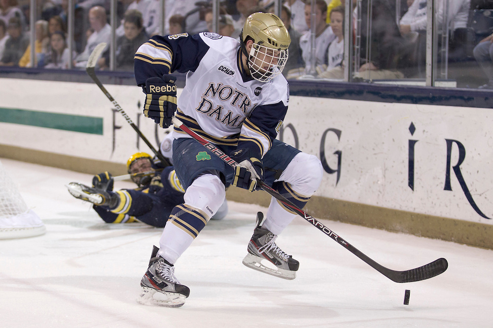 Notre Dame center Riley Sheahan (#4) controls the loose puck in second period action of NCAA hockey game between Notre Dame and Michigan.  The Notre Dame Fighting Irish  defeated the Michigan Wolverines 3-1 in game at the Compton Family Ice Arena in South Bend, Indiana.