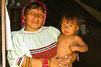 Kuna Indian woman wearing native costume (with Mola embrodery blouse) holding her child in her hut, Crab Island (Carti Sugdup), San Blas Islands (Kuna Yala), Caribbean Sea, Panama