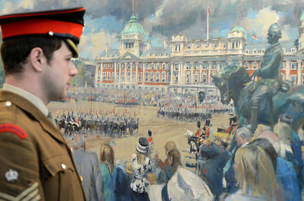 © Licensed to London News Pictures. 20/04/2012. London, UK . Lance Corporal John Brophy looks at The March Past, Queen's Birthday by Tom Hoar. A Preview of the Household Cavalrys 'The Best of British' art exhibition. Soldiers walk around the artwork as they prepare to mount duties at Horse Guards Parade. The Queen's Life Guard are inspected before they depart the Barracks for the daily Guard change at 1100. The exhibition runs between 23 - 26 April. Hyde Park Barracks, Ceremonial Gate, South Carriage Drive, London, SW7 1SE. Photo credit : Stephen Simpson/LNP