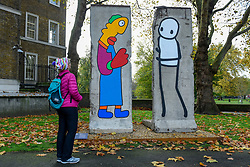 © Licensed to London News Pictures. 05/11/2019. LONDON, UK.  A woman views new work by artists Theirry Noir (L) and STIK (R) on original Berlin Wall sections to mark 30 years since the fall of the Berlin Wall.  Located outside the Imperial War Museum, the new works reflect the symbolic connections between the Berlin Wall and street art and the fall of the wall on 9 November 1989.  These new works are on display until 1 December.  Photo credit: Stephen Chung/LNP