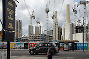 A man walks past a pub opposite  Battersea Power Station in London, United Kingdom on 6th August 2019. Battersea Power Station is a decommissioned coal-fired power station on the south side of the River Thames.The site is being redeveloped into residential units, bars, restaurants, office space, shops and entertainment spaces.