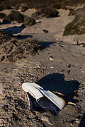 Discarded shoe on Balos Beach, on Gramvousa peninsula, in north western Crete, Greece. The beach is famous for its white sands and turquoise waters and is a protected nature reserve.