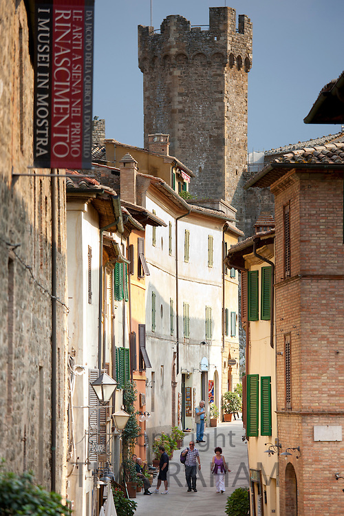 Visitors walking in Via Ricasoli in old hill town of Montalcino, Val D'Orcia,Tuscany, Italy