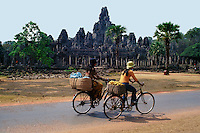 Cambodian cyclists pass the Bayon, a richly decorated Khmer temple at Angkor in Cambodia. Built in the late 12th century or early 13th century as the official state temple of the Buddhist King Jayavarman VII, the Bayon stands at the centre of Jayavarman's capital, Angkor Thom.