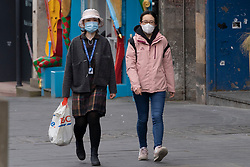 Edinburgh, Scotland, UK. 29 April 2020. Views of Edinburgh Old Town as coronavirus lockdown continues in Scotland. Streets remain deserted and shops and restaurants closed and many boarded up. Scottish Government now recommends public to wear face masks. Pictured. Two asian women walking on Royal Mile wearing face masks.  Iain Masterton/Alamy Live News
