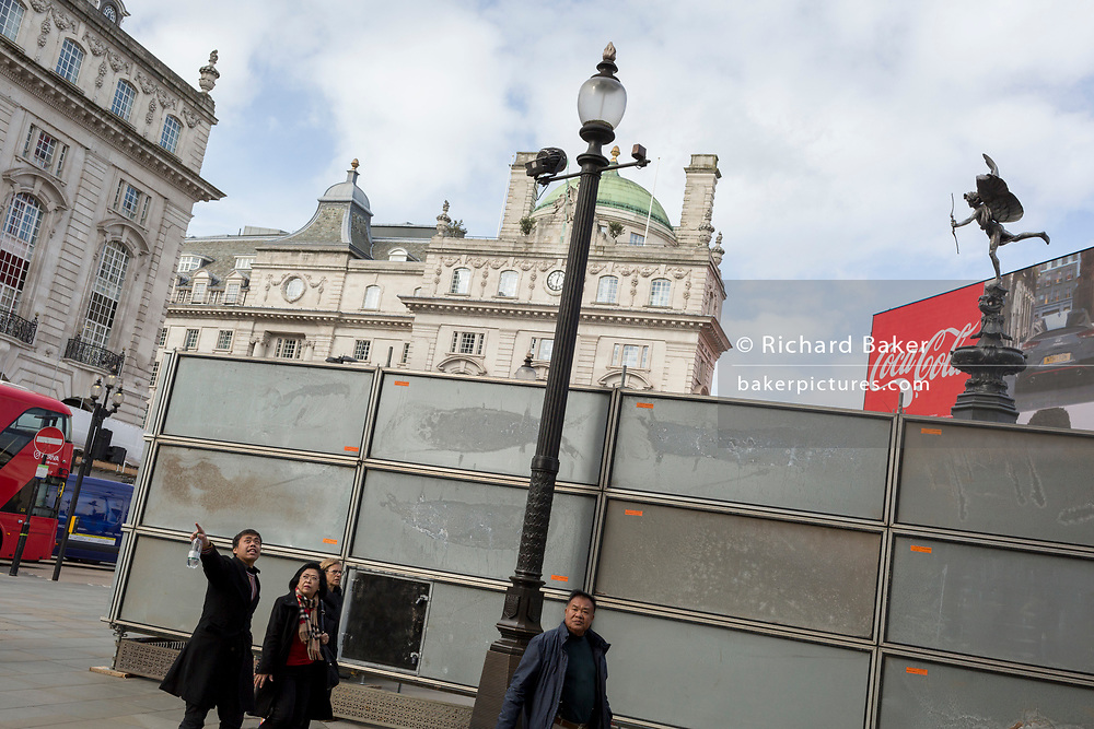 "A pedestrian points towards a London site next to a temporary construction hoarding beneath the partially hidden statue of the world famous London Victorian-era landmark, Eros in Piccadilly Circus, on 25th February 2020, in London, England. Eros, or the Shaftesbury Memorial Fountain is located at the southeastern side of Piccadilly Circus in London, United Kingdom. Moved after World War II from its original position in the centre, it was erected in 1892–1893 to commemorate the philanthropic works of Lord Shaftesbury, who was a famous Victorian politician and philanthropist. The monument is surmounted by Alfred Gilbert's winged nude statue generally, though mistakenly, known as Eros. This has been called ""London's most famous work of sculpture."""