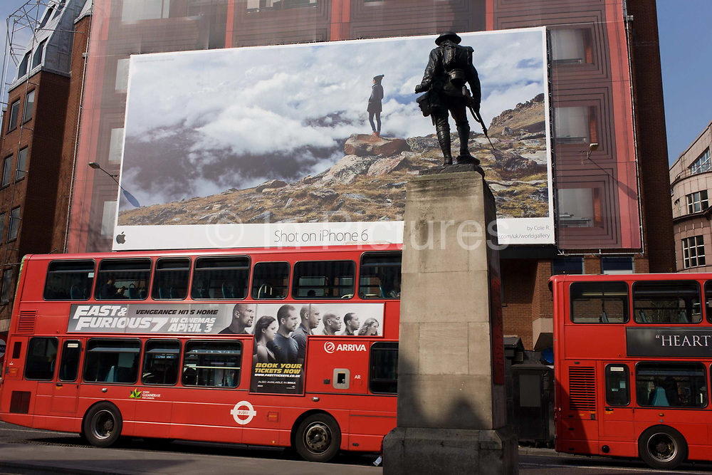 A giant billboard ad for the use of iPhones seen on the side of a central London building, juxtaposed with bus advertising and a WW1 memorial soldier of the Royal Fusiliers. The two buses are stopped in traffic on the road, one with the advertising of yet another Hollywood action film opening soon. The huge image on the side of the building is in the City of London and features a young woman standing on a mountain top looking out across the clouds at altitude. The Infrantryman stands at rest on the top of the memorial, a reminder of lost youth and possibilities from an era of sacrifice before consumerism a hundred years later.