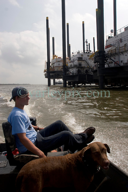 25 Sept, 2005.   Lake Calcasieu, Louisiana.  Hurricane Rita aftermath. <br /> Oil industry rig support platforms prepare to put to sea to repair damaged rigs in the Gulf of Mexico to keep the oil flowing to the U.S. mainland. local man Aaron Stokes and his dog Maggie pass by the platforms.<br /> Photo; ©Charlie Varley/varleypix.com
