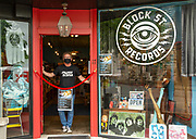 Wade Ogle, owner of Block Street Records, stands in the doorway of his store on Wednesday, May 17, 2019, in Fayetteville, Ark. Ogle has a rope across the front door with rules for entering the store during the Covid-19 pandemic.<br /> <br /> Photo by Beth Hall for the New York Times<br /> <br /> NYTVIRUS