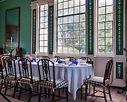 Inside the Mount Vernon house, a dining table with place settings is depicted as in 1799, the last year of Washington's life. Mount Vernon, Virginia, was the plantation home of George Washington, the first President of the United States (1789-1797). The mansion is built of wood in neoclassical Georgian architectural style on the banks of the Potomac River. Mount Vernon estate was designated a National Historic Landmark in 1960 and is owned and maintained in trust by The Mount Vernon Ladies' Association. The estate served as neutral ground for both sides during the American Civil War, although fighting raged across the nearby countryside. George Washington, who lived 1732-1799, was one of the Founding Fathers of the United States of America (USA), serving as the commander-in-chief of the Continental Army during the American Revolutionary War, and presiding over the convention that drafted the Constitution in 1787. Named in his honor are Washington, D.C. (the District of Columbia, capital of the United States) and the State of Washington on the Pacific Coast.