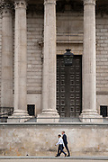 Two men walk beneath the pillars and column architecture of Sir Christopher Wren's St Paul's Cathedral south transept, on 24th June 2021, in London, England. CREDIT RICHARD BAKER.