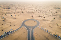Aerial view of roundabout covered with sand in the desert of Dubai, UAE.