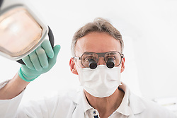 Close-up of male dentist wearing magnifiers on eyeglasses, Munich, Bavaria, Germany