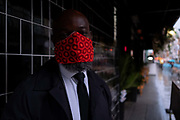 On a rainy night in Soho, security man H  wears a bright red facial covering outside a business at a time when recently re-opened bars and restaurants are desperate for customer business during the coronavirus pandemic, on 27th August 2020, in London, England.