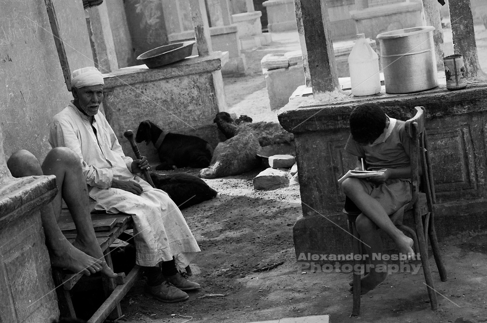 Cairo, Egypt, The City of the Dead, 1998 - Boy doing school work in front of graves.