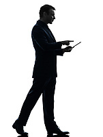 one  business man walking touchscreen digital tablet in silhouette on white background