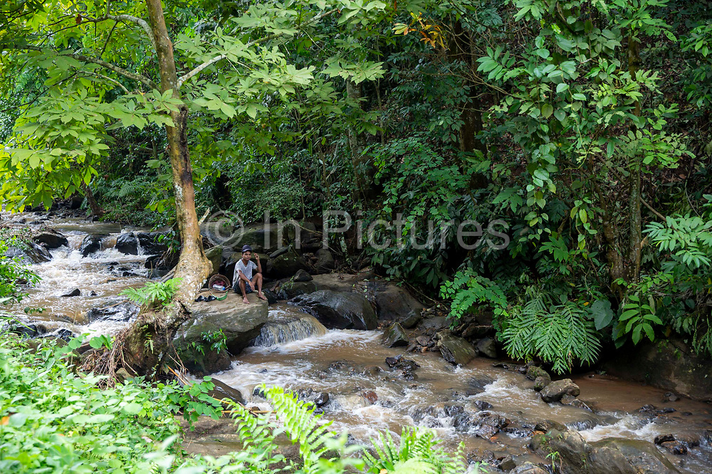 A man rests and sits on a large stone in a flowing river on 21st September 2018 in Umling, Ri Bhoi, Meghalaya, India.