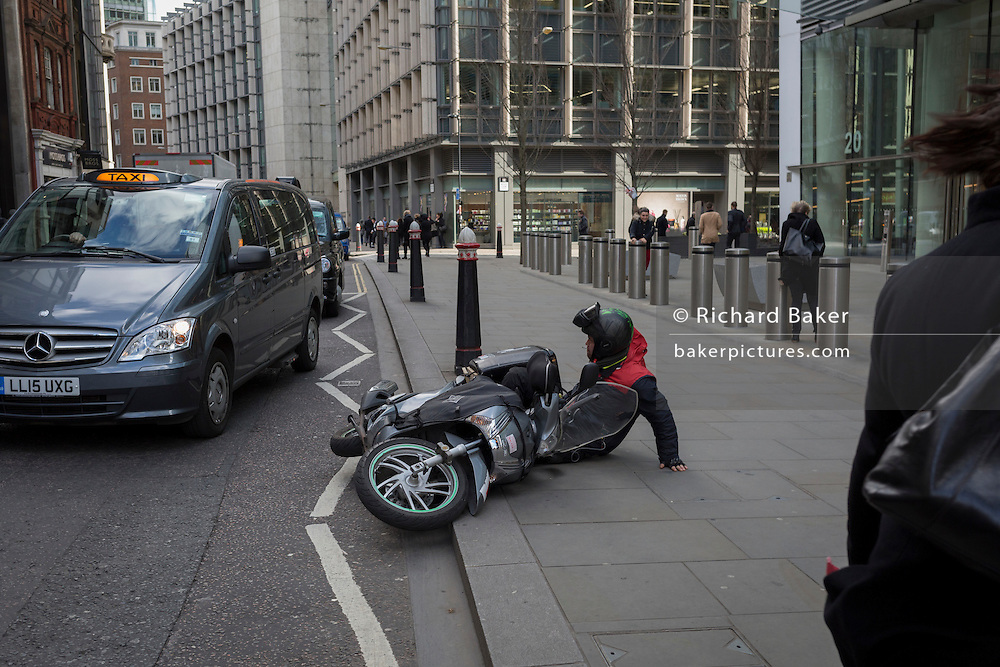 A cyclist struggles to his feet after being blown over by a gust of wind as Storm Doris blows across the UK and pedestrians on Fenchurch Street, brave the high winds funneled through the narrow streets, squeezed between the tall buildings of financial and insurance institutions in the City of London, on 23rd February 2017. Strong winds have led to flight cancellations and road and rail disruption across much of Britain. Thousands of homes have been left without power in Northern Ireland, Wales, Scotland and northern England.