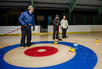 Dick Pease gives two points to Polly Doucet and Margo Weeks of the yellow team during the Gilford Parks and Recreation first night of curling at the Gilford Ice Rink Thursday.   (Karen Bobotas/for the Laconia Daily Sun)