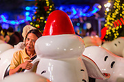 17 DECEMBER 2014 - BANGKOK, THAILAND: A woman hugs a Snoopy wearing a Santa Claus hat at the Christmas display in front of Central World in Bangkok. Thailand is overwhelmingly Buddhist. Christmas is not a legal holiday in Thailand, but Christmas has become an important commercial holiday in Thailand, especially in Bangkok and communities with a large expatriate population.    PHOTO BY JACK KURTZ