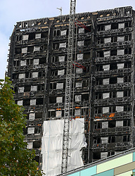October 14, 2017 - London, London, United Kingdom - Image ©Licensed to i-Images Picture Agency. 14/10/2017. London, United Kingdom. Work Begins To Cover Grenfell Tower...Scaffolding has been put up alongside Grenfell Tower in west London in preparation for a white sheet covering to shield it's view from the public. Around 80 people died and hundreds were left homeless during the disaster on 14 June 2017, four months ago. Investigators will remove remnants of the cladding, which fuelled the fire on the tower block. ..Picture by Dinendra Haria / i-Images (Credit Image: © Dinendra Haria/i-Images via ZUMA Press)