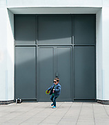 A young boy chases a pigeon outside a closed shop during the first UK national lockdown in April 2019. Credit: Oliver Norcott/UoG/PathosImages