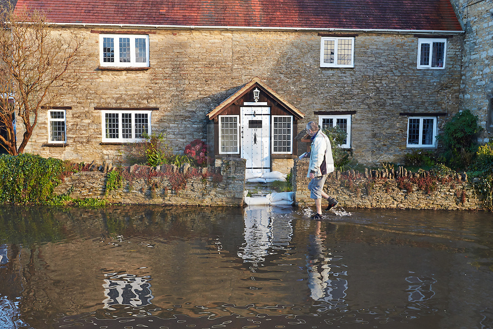 © Licensed to London News Pictures.  23/11/2012. OXFORD, UK. A man walks through a flooded road in Kidlington, near Oxford. Overnight heavy rain has caused numerous floods. Photo credit :  Cliff Hide/LNP