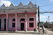 Pink building colonial architecture with an old man walking past with a bicycle and wearing a stetson hat, in the centre Palmira village in Cienfuegos province, Cuba.