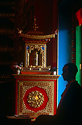 A nun practicing Tibetan-Buddhism meditates in silence at a shrine. Seen in almost silhouette, the young woman engages in Puja, or prayer, at the Kagyu Samye Ling Buddhist retreat centre in Eskdalemuir, Scotland. She is a western visitor, many of whom have had a troubled youth and are sometimes escaping a criminal past, who arrive in the Scottish wilderness for isolated retreat periods, for short-term spiritual relaxation or to follow Tibetan teaching methods for discovering inner-peace, through prayer and meditation. This Tibetan Buddhist complex associated with the Kagyu School celebrated its 40th anniversary in 2007.