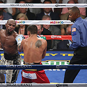 LAS VEGAS, NV - SEPTEMBER 13: Floyd Mayweather Jr. (L) jabs at Marcos Maidana as referee Kenny Bayless watches, during their WBC/WBA welterweight title fight at the MGM Grand Garden Arena on September 13, 2014 in Las Vegas, Nevada. (Photo by Alex Menendez/Getty Images) *** Local Caption *** Floyd Mayweather Jr; Marcos Maidana; Kenny Bayless
