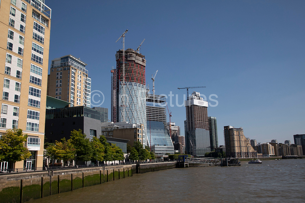 Construction of new 60 storey residential tower block Newfoundland at Canary Wharf financial district in London, England, United Kingdom. Newfoundland is a 60-storey residential building which will be situated on the western side of the Canary Wharf Estate and bound by Westferry Road to the west, Middle Dock to the east, and Bank Street to the south. The slim diamond shape of the tower is determined by the narrow footprint of the site. The dia-grid structural system expressed on the facade of the building supports and braces the structure.