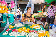 09 OCTOBER 2012 - BANGKOK, THAILAND:  A woman makes flower garlands at the Bangkok Flower Market. The Bangkok Flower Market (Pak Klong Talad) is the biggest wholesale and retail fresh flower market in Bangkok. It is also one of the largest fresh fruit and produce markets in the city. The market is located in the old part of the city, south of Wat Po (Temple of the Reclining Buddha) and the Grand Palace.    PHOTO BY JACK KURTZ
