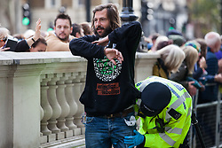 London, UK. 9 October, 2019. Police officers arrest George Barda, a climate activist from Extinction Rebellion, who had locked himself to another activist using an arm tube to block Whitehall on the third day of International Rebellion protests.