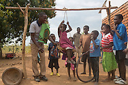 Volunteer teacher, Bright Kachepa, helps students on the swings outside the Alinafe Community Based Childcare Center in Mjambe Village near Zomba, Malawi. The volunteer teachers who run the centers have received training from a local CRS project through a Conrad N. Hilton Foundation grant. The project known as THRIVE focuses on early childhood development and includes special support for childcare centers, children's health and nutrition and lessons in positive parenting. The Alinafe center started under a tree and is now a full fledged building.