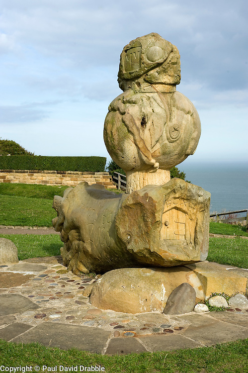 Sculpture in rock stands at the top of the cliff looking out to sea from Robin Hoods Bay north Yorkshire.September 2010 .Images © Paul David Drabble