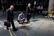 An unknown official measures heat in a pavement hotspot as Londoners experience the unexpected intensity of solar rays, reflected off concave plate glass windows of one of the capital's newest skyscrapers. The hotspot has surprised developers and passers-by below and which has already melted a parked car in Eastcheap Street in the City of London. Thermometers placed in the street reached 144F (62 celcius) and city workers in poured out of their offices at lunchtime to experience the intense light and heat.