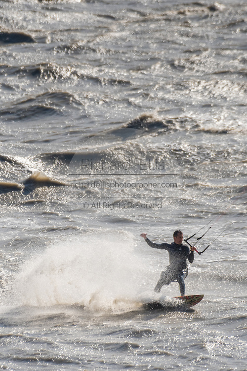 A kite surfer rides waves caused by the bore tide on Turnagain Arm at Windy Point outside Anchorage, Alaska.