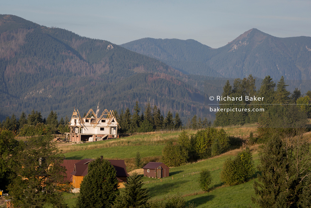 An aerial landscape of new housing that is overlooked by the Tatra mountains in the Polish town of Koscielisko, on 16th September 2019, near Zakopane, Malopolska, Poland. Local wealth has encouraged tourism apartments and short-stay properties in the Zakopane and Tatra National Park region, a very popular outdoor activity destination for city-dwelling Poles but at the cost of the local environment and landscape.