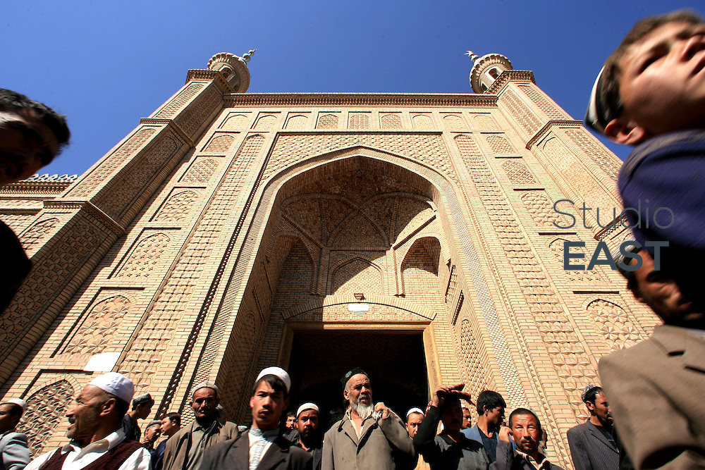 XINJIANG PROVINCE, CHINA - October 13: Muslims exit Hetian mosque after the Friday prayer on October 13, 2006 in Hetian, Xinjiang province, China. The Uyghur people are a Turkic ethnic group living mainly in the Xinjiang Uyghur Autonomous Region of China. (Photo by Servais Mont/Getty Images)