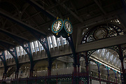 Ironwork and ornate clock hanging from the roof of Smithfield meat and poultry market in Clerkenwell, London. Smithfield Market, a Grade II listed-covered market building, was designed by Victorian architect Sir Horace Jones, completed in November 1868 at a cost of £993,816 (£80 million at 2015 prices).