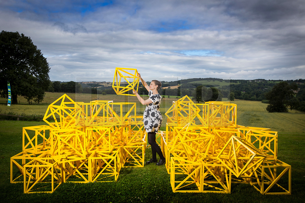 """© Licensed to London News Pictures. 14/07/2017. Wakefield UK. Kerry chase looks at the Zero to Infinity sculpture by Rasheed Araeen which is part of the new exhibition """"Occasional Geometries"""" curated by Bangladeshi-born artist Rana Begum at the Yorkshire Sculpture park in Wakefield, the exhibition is largely selected from the Art's Council Collection & is designed to create an architectural, spatial & Playful experience through colour, movement & changing light.. The new exhibition is part of the Yorkshire Sculpture Parks 40th anniversary celebration """"A weekend of wonderful things"""" Photo credit: Andrew McCaren/LNP"""