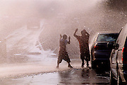 Kids play in the warm weather as a fire hydrant sprays them on East 97th Street in Manhattan, NY. 8/9/2001