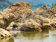 12 MARCH 2016 - LUANG PRABANG, LAOS:  A man does subsistence fishing in the Nam Khan River near its confluence with the Mekong River in Luang Prabang, Laos. Laos is one of the poorest countries in Southeast Asia. Tourism and hydroelectric dams along the rivers that run through the country are driving the legal economy.      PHOTO BY JACK KURTZ
