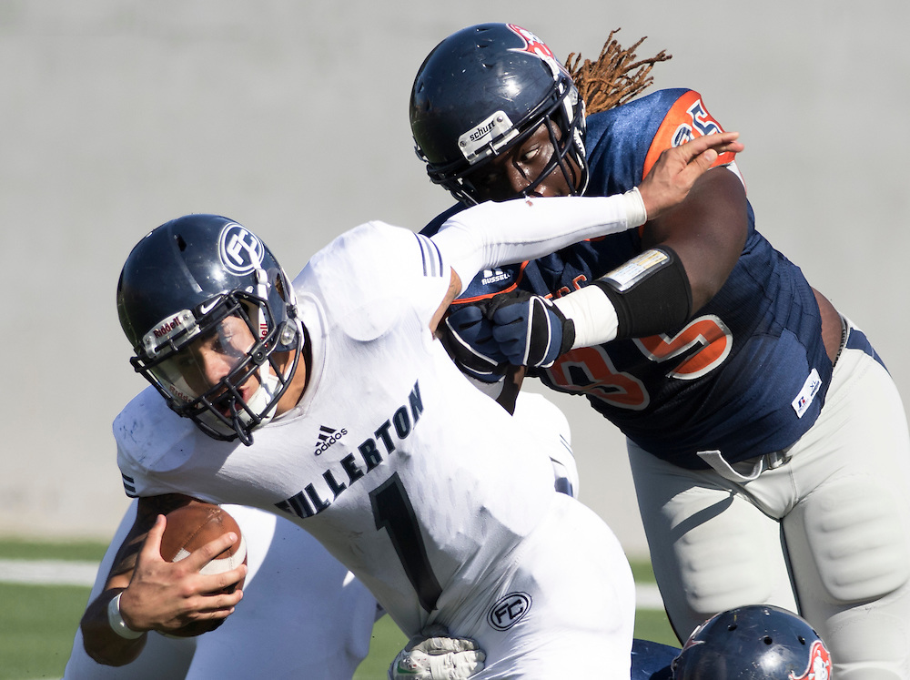 Fullerton College, quarterback Jordan Hoy (1), is tackled by Orange Coast College defensive lineman, Keith Ford (95) during a CCCAA football game in Costa Mesa, California on November 5.<br /> Photo by Rachel Lacey Noll, Sports Shooter Academy