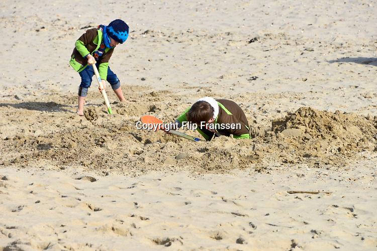Nederland, Ter Heijde, 26-3-2018De zandmotor is een opgespoten zandvlakte voor de kust op een kwetsbare plek. Dit schiereiland zorgt ervoor dat de kust tussen Hoek van Holland en Scheveningen op natuurlijke wijze aangroeit waardoor het meer bescherming geeft tegen de zeespiegelstijging. Mensen, recreanten, wandelen of laten hun hond uit .  Kinderen graven een kuil in het zand op het strand .Foto: Flip Franssen