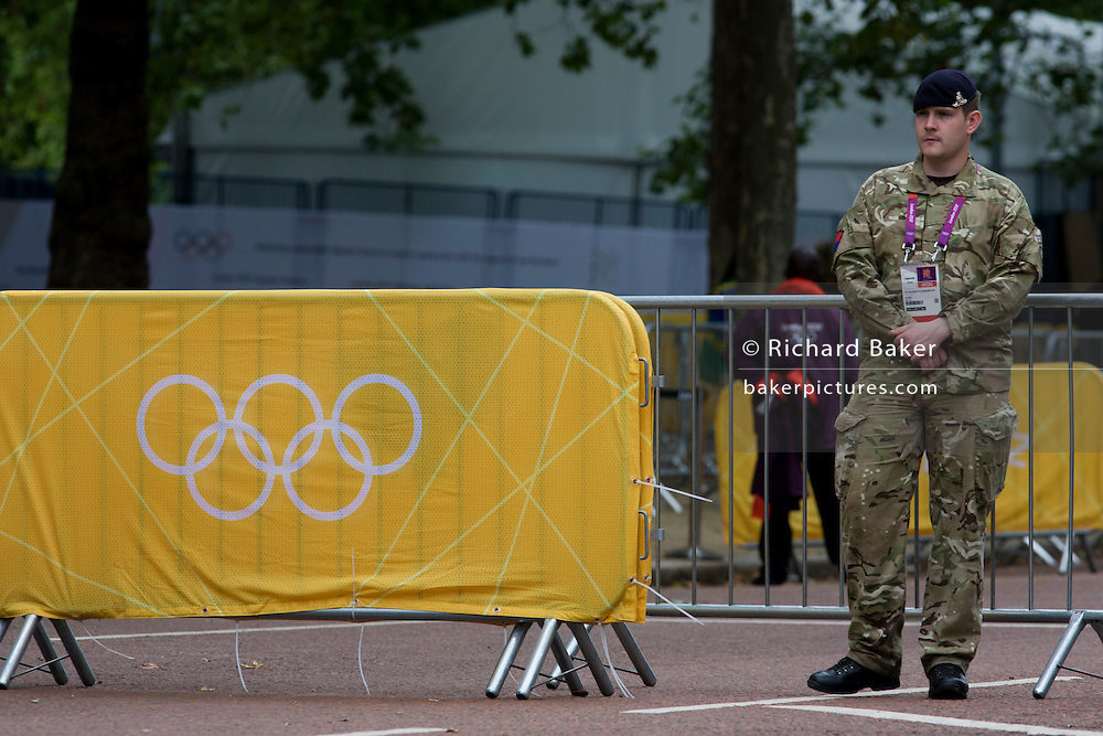 A soldier of the Royal Artillery regiment in the British army stand guarding the entrance to  the volleyball venue in central London next to the IOC rings logo on day 4 of the London 2012 Olympic Games. A total of 18,000 defence personel were called upon to make the Games secure following the failure by security contractor G4S to provide enough private guards. The extra personnel have been drafted in amid continuing fears that the private security contractor's handling of the £284m contract remains a risk to the Games.