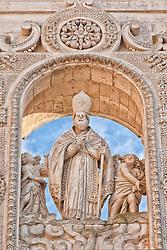 La cattedrale metropolitana di Santa Maria Assunta è il principale luogo di culto cattolico di Lecce, chiesa madre dell'arcidiocesi metropolitana omonima. Si trova in piazza del Duomo, nel centro storico della città. Una prima cattedrale della diocesi di Lecce venne costruita nel 1144 dal vescovo Formoso. Nel 1230, per volere del vescovo Roberto Voltorico, la cattedrale venne rinnovata e ricostruita in stile romanico..Nel 1659, il vescovo di Lecce Luigi Pappacoda diede all'architetto leccese Giuseppe Zimbalo, detto lo Zingarello, il compito di ricostruire la chiesa cattedrale in stile barocco leccese. L'architetto scelse di non alterare la pianta della cattedrale romanica e la prima pietra venne posata il 1º gennaio dello stesso anno. La costruzione venne portata avanti dal 1659 fino al 1670, quando la nuova cattedrale venne solennemente consacrata dal vescovo Pappacoda. Il tempio possiede due prospetti, di cui il principale è quello a sinistra dell'Episcopio, mentre l'altro guarda l'ingresso della piazza..La facciata principale, piuttosto semplice sotto il profilo decorativo, si sviluppa in due ordini dove sono presenti le statue, alloggiate in nicchioni, dei Santi Pietro e Paolo, di San Gennaro e di San Ludovico da Tolosa. La disposizione delle paraste scanalate fa intravedere che la chiesa è strutturata in tre navate..Il prospetto settentrionale, ricco ed esuberante, assolve a una precisa funzione scenografica, dovendo rappresentare l'ingresso principale della chiesa per chi entra nel sagrato. Scompartito in cinque zone da paraste e colonne scanalate, il primo ordine presenta un portale ai cui lati due nicchie ospitano le statue di San Giusto e di San Fortunato. La trabeazione è coronata da un'alta balaustra alternata da colonnine e pilastrini, oltre la quale, al centro, si innalza la statua di Sant'Oronzo.
