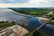 Nederland, Noordoostpolder, Flevoland, 30-06-2011. Ramspol, Waterkering Kampen, tussen Ketelmeer en Zwarte Water. Rechts Ramsdiep en Noordoostpolder. De balgstuw is een stormvloedkering en bestaat uit een opblaasbare dam of dijk, opgebouwd uit drie balgen. In niet-opgeblazen toestand liggen de balgen op de bodem. Naast de stuw grondwerk voor de nieuwe dubbelbaans Ramspolbrug..Ramspol, inflatable dike, between Ketelmeer and Black Water. The Balgstuw (bellow barrier) is a storm barrier and consists of an inflatable dam or dyke, composed of three bellows. Usually, each bellow rests on the bottom of the water...luchtfoto (toeslag), aerial photo (additional fee required).copyright foto/photo Siebe Swart