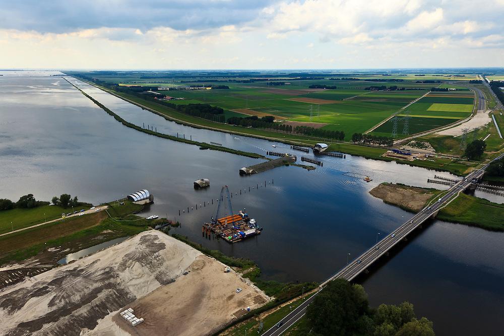 Nederland, Noordoostpolder, Flevoland, 30-06-2011. Ramspol, Waterkering Kampen, tussen Ketelmeer en Zwarte Water. Rechts Ramsdiep en Noordoostpolder. De balgstuw is een stormvloedkering en bestaat uit een opblaasbare dam of dijk, opgebouwd uit drie balgen. In niet-opgeblazen toestand liggen de balgen op de bodem. Naast de stuw grondwerk voor de nieuwe dubbelbaans Ramspolbrug..Ramspol, inflatable dike, between Ketelmeer and Black Water. The Balgstuw (bellow barrier) is a storm barrier and consists of an inflatable dam or dyke, composed of three bellows. Usually, each bellow rests on the bottom of the water...luchtfoto (toeslag), aerial photo (additional fee required).copyright foto/photo Siebe Swart