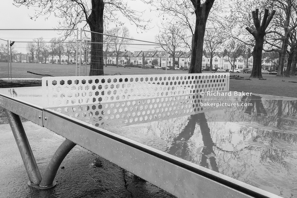 Ruskin Park's single table-tennis table, a facility owned by Lambeth council in south London, remains un-used on a cold and wet Saturday morning during the third lockdown of the Coronavirus pandemic, in on 30th January 2021, in London, England.